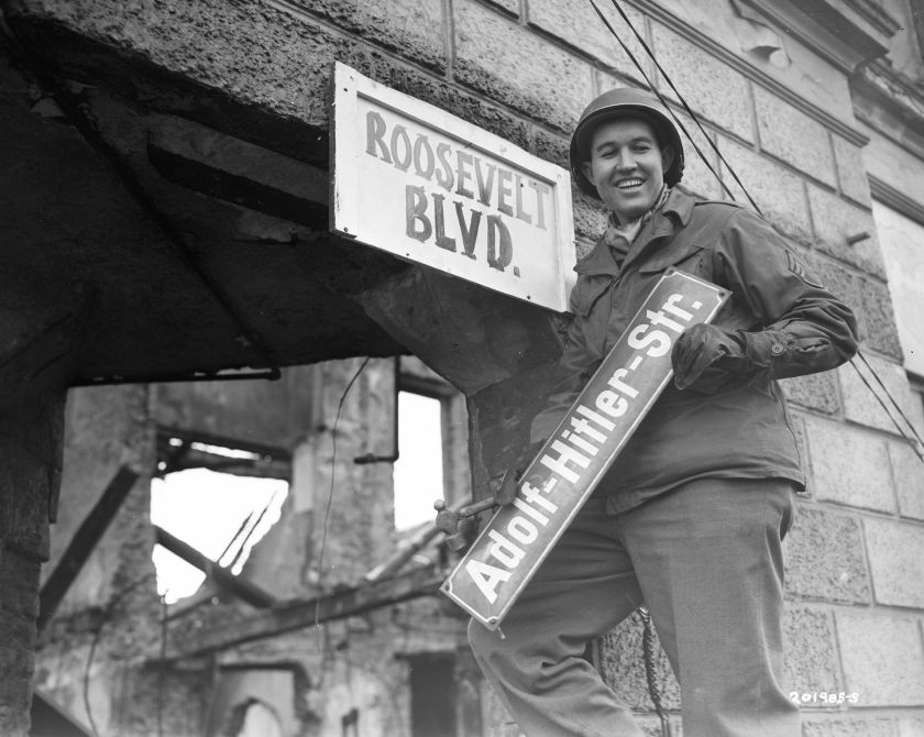 A man removes the sign for Adolf Hitler Street""